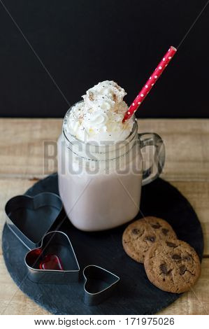 Vertical photo of hot chocolate with whipped cream topping and red paper straw served on a trendy slate board with two chocolate cookies and hearts. Love and romantic concept. Romantic breakfast