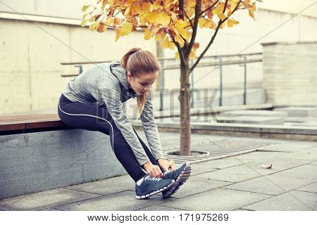fitness, sport, friendship and lifestyle concept - happy young sporty woman tying shoelaces outdoors