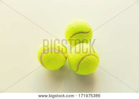 sport, fitness, game and objects concept - close up of three yellow tennis balls