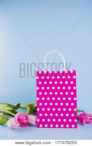 Crimson Shopping Bag With Bouquet Of Pink Tulips On Blue Wooden Background
