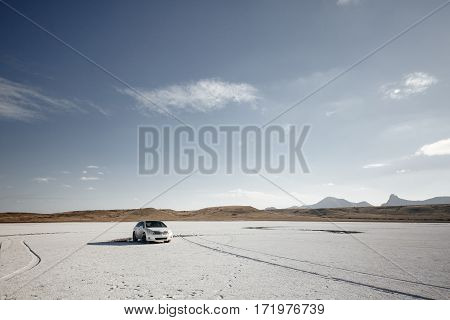 Car on a salt lake in the vicinity of the acute mountain