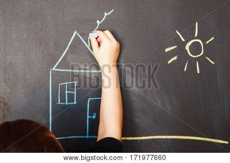 a child draws on blackboard chalk house