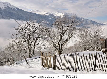 wooden fence in a garden covered by snow in mountain