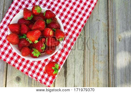 Spring fruits strawberries in a paper bag on an old wooden background.