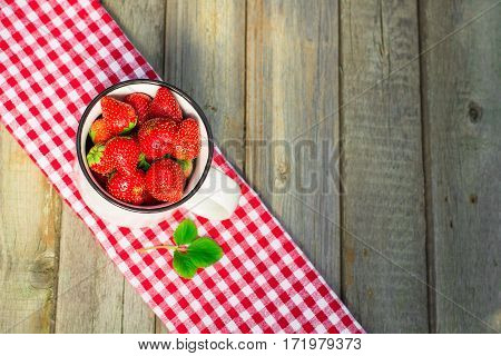 Strawberries In A Paper Bag On An Old Wooden Background.