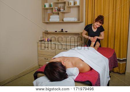 massage therapist doing wellness foot massage at spa salon, while woman lying on a massage table