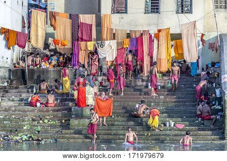 People Cleaning Clothes And Washing In The River Ganges In Calcutta, India