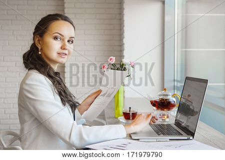 Confident woman holding document in hand and typing on computer. Businesswoman reviewing paper with chart making investment researches. Growth of sales, planning and investment concept.