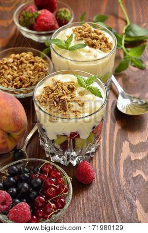 Dessert with fresh berries granola and custard in glasses, vertical