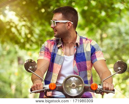 Handsome Young Man In Sunglasses Sitting On A Scooter