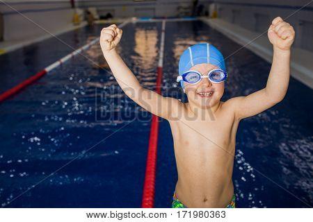 Boy swimmer enjoys, raising both hands up, behind his swimming pool. Gesture of winner