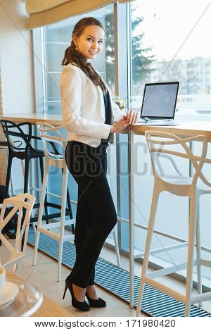 Business woman stands near high table with laptop. Desktop illuminates by daylight of large window across the room height.
