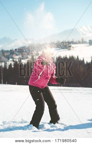 Woman throwing the snow in the air