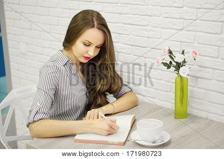 Sympathetic girl holding elegant pen and writing in sketchbook. Empty cup on saucer and vase with pastel flower stands on table.