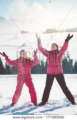 Mother enjoying the snow with her daughter outdoors in the wintertime