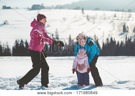 Mother playing with her children outdoors in the wintertime