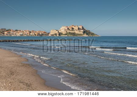 Waves Lapping Onto Calvi Beach With Citadel And Town Behind