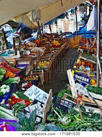 Venice Italy- February 26th 2011: Image of a floating vegetables and fruits market in a boat on a small canal in Venice.