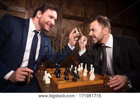 Rich businessmen playing chess demonstrating rivalry or competition. Two executive men have competition between their enterprises, companies, firms. Big business concept.