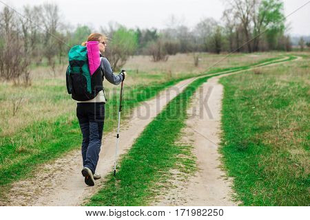 Backpacker woman with trekking pole in hand , walking with a backpack. ahead her rural road