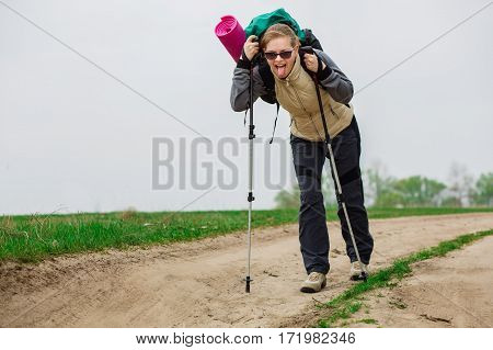 tired woman with trekking pole in hand , walking with a heavy backpack outdoors