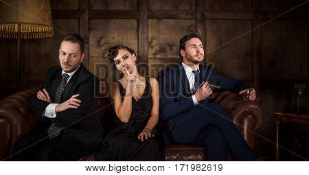 Rivalry or competition between two handsome rich executive men for elegant lady with red lips. Beautiful people sitting on sofa in restaurant. Richness, wealth, luxury concepts.