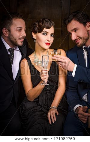 Focus on pretty lady with red lips sitting with glass of champagne. Two handsome rich executive businessmen have rivalry or competition for elegant lady in restaurant atmosphere.