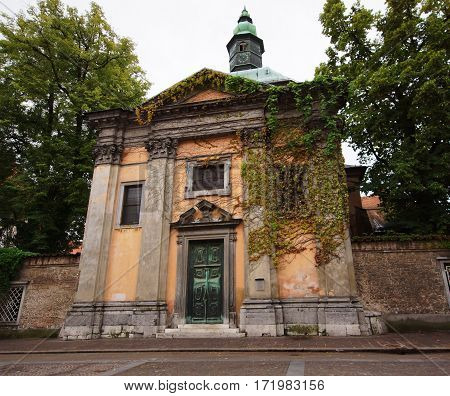 an orange building overgrown with ivy with a brick wall on both sides in the capital of Slovenia Ljubljana