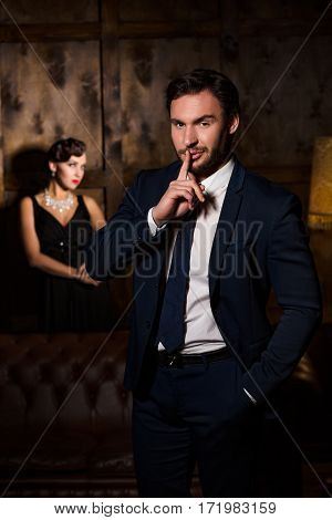 Wealth, luxury concepts. Handsome man asking for silence and keeping hand in pocket. Elegant gorgeous lady sitting on background.