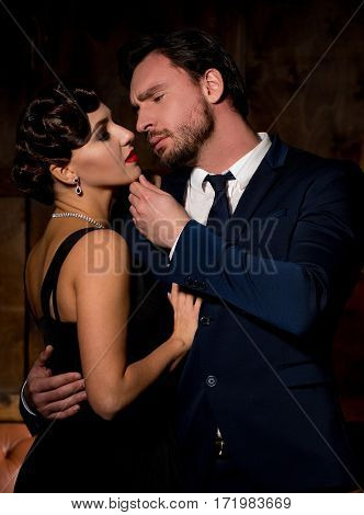 Passion concept. Handsome businessman hugging lady and touching her chin. Vamp woman with red lips looking at camera and dreaming about marrying millionaire man.