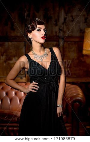 Vamp lady with red lips posing for photographer in restaurant. Elegant lady in black dress posing with her hand on hip.