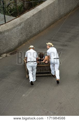 FUNCHAL PORTUGAL - SEPTEMBER 2 2016: Toboggan riders moving traditional cane sledge downhill on the streets of Funchal.