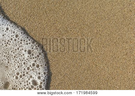 Texture of sand with soft wave close up