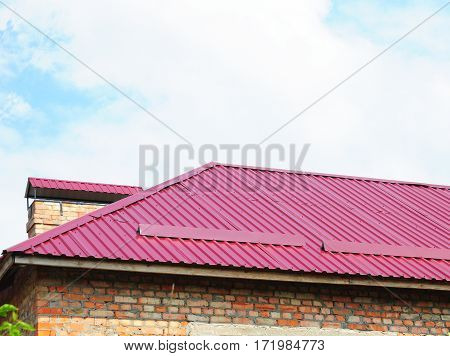 Roofing construction. Close up on metal roofing with roof protection from snow board snow guard on house construction. Red metal roof.