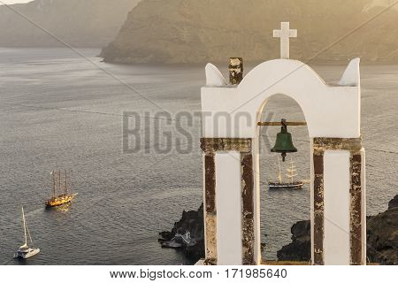 Traditional church belfry and sailing boats at sunset in Oia Santorini Greece