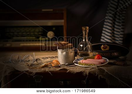 Carafe with alcohol and snacks lying on a suitcase with his cap and vest on a background of an old radio receiver