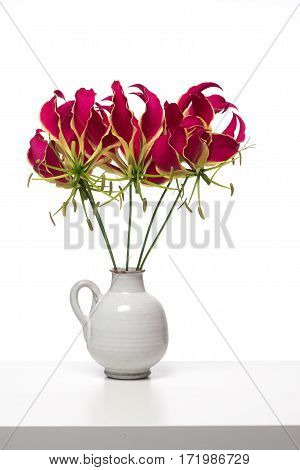 Bouquet of gloriosa glory lilies flowers at a white shelf at a white background