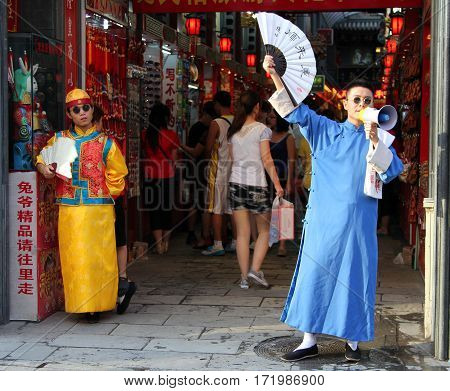 Beijing, China - Jul 3, 2011: Stylish Greeters At The Entrance To The Market Of Souvenirs At Dazhala