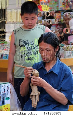 Beijing, China - Jul 3, 2011: Craftsman Making Souvenirs On Dazhalan Commercial Street, Not Far From