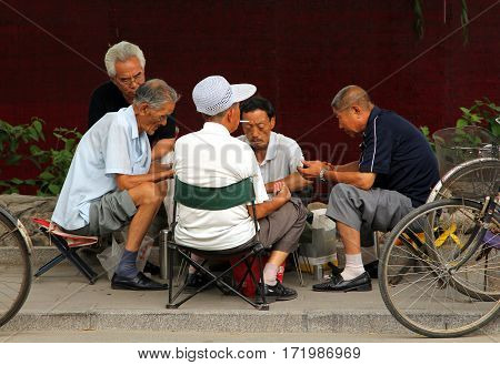 Beijing, China - Jul 5, 2011: Chinese Men Playing Mahjong (or Majiang, Very Popular Chinese Game) In