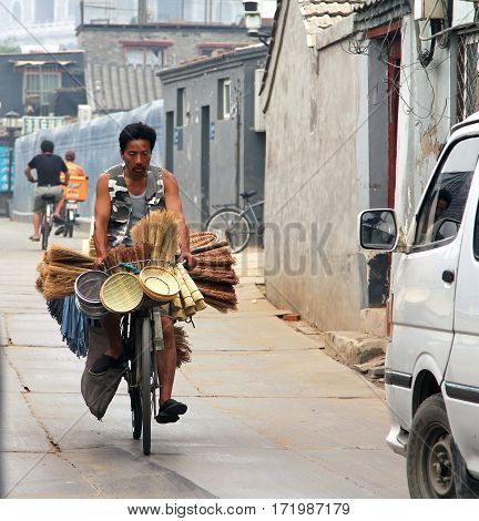 Beijing, China - Jul 5, 2011: Merchant Of Household Utensils Carring His Goods On A Bicycle. Bicycli