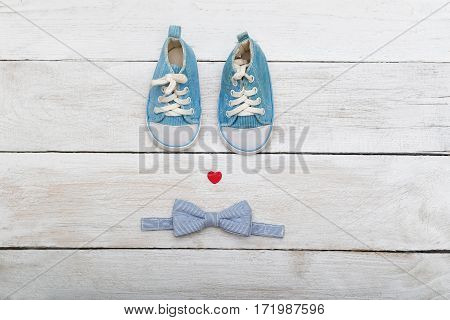 Blue shoes for a small baby and a butterfly-tie on wooden background. View from above