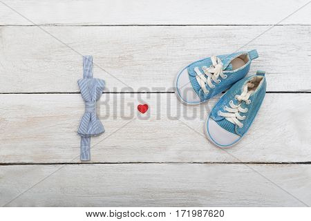 shoes and a butterfly-tie for a young boy on a wooden background.