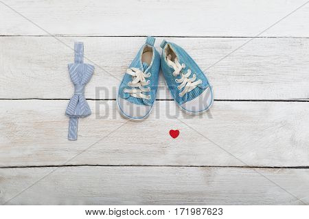 shoes and a butterfly-tie for the boy on a wooden background. Flat lay