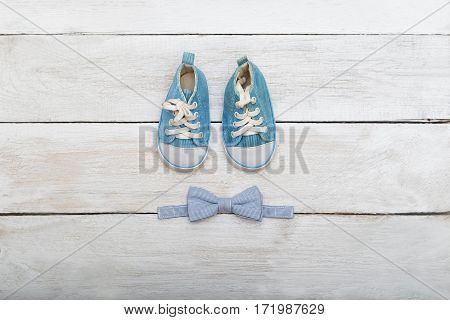 shoes and a butterfly-tie for the boy on a wooden background. View from above