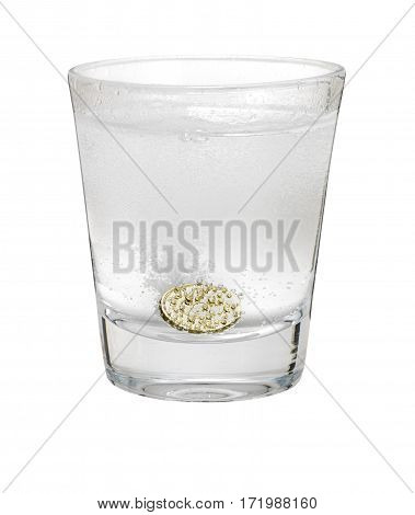 Pound coin like alka seltzer dissolving in glass isolated on white