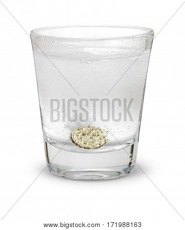 Pound coin like alka seltzer dissolving in glass isolated on white with shadow