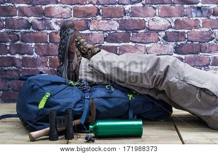 Close Up of One Person who wears boots for trekking and Mountain with close Tools and Accessories as a compass backpack drinking bottle and ax Rock