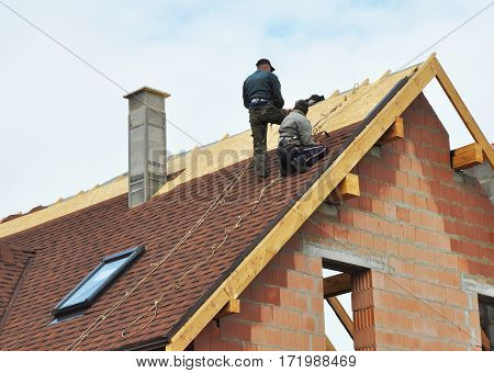 KYIV, UKRAINE - March 1, 2017:  Building contractors putting the asphalt roofing. Roofers laying tiles on the roof while roofing a house outdoor. Roofers Install Repair Asphalt Shingles or Bitumen Tiles on the Rooftop Outdoor.