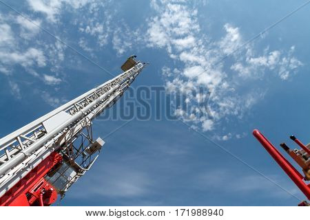 Sliding fire ladder against cloudy, blue sky